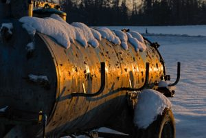 Dung cart in snow in glow of setting sun